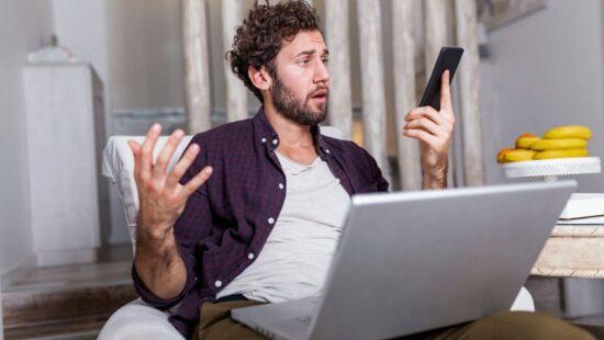 Ein Mann verzweifelt vor seinem Computer und seinem Smartphone, was er in der Hand hält.