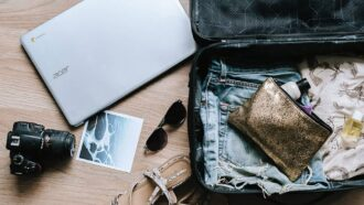 Koffer mit Urlaubsutensilien, Kamera und Laptop