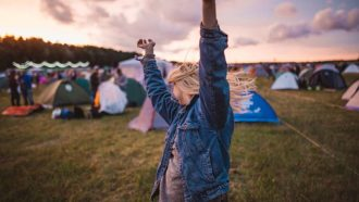 Ein junges Mädchen auf einem Festival freut sich und reißt die Arme nach oben.