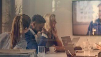 Vier Menschen und ein Monitor mit einer Video-Konferenz