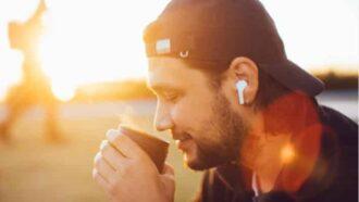 Mann mit Kaffee und EarPods vor der aufgehenden Sonne