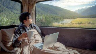 Ein junger Mann sitzt mit Laptop und Kaffee in seinem Camper-Van und schaut in die Natur.