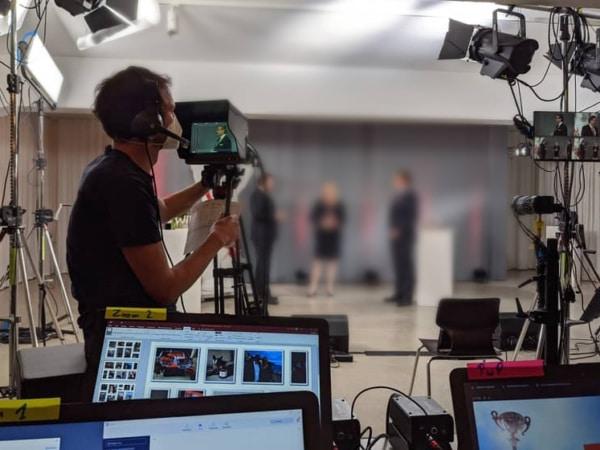 Ein Kameramann von Eventnet filmt eine Diskussion von drei Menschen bei einer Livestreaming-Produktion